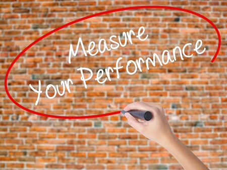 Woman Hand Writing Measure Your Performance with black marker on visual screen. Isolated on bricks. Business concept. Stock Photo Stock Photo