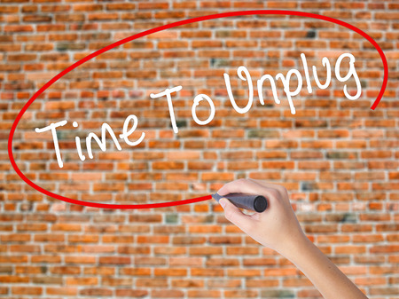 Woman Hand Writing Time To Unplug with black marker on visual screen. Isolated on bricks. Business concept. Stock Photo