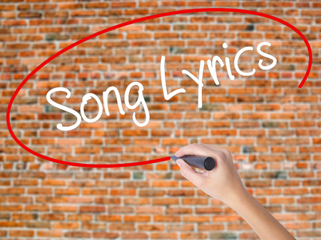 music lyrics: Woman Hand Writing Song Lyrics with black marker on visual screen. Isolated on bricks. Business concept. Stock Photo Foto de archivo