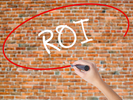 Woman Hand Writing ROI (Return on Investment)  with black marker on visual screen. Isolated on bricks. Business concept. Stock Photo