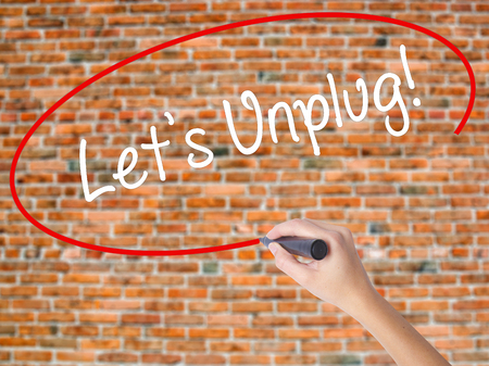 Woman Hand Writing Lets Unplug! with black marker on visual screen. Isolated on bricks. Business concept. Stock Photo Stock Photo