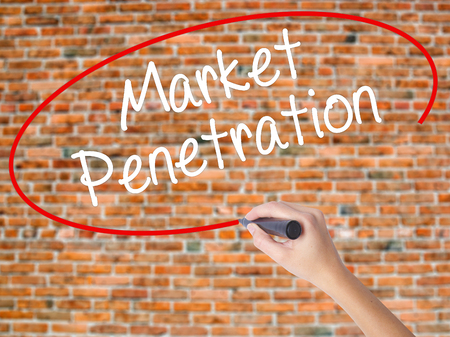 Woman Hand Writing Market Penetration with black marker on visual screen. Isolated on bricks. Business concept. Stock Photo
