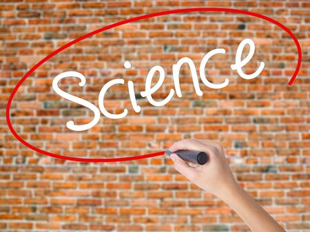 Woman Hand Writing Science with black marker on visual screen. Isolated on bricks. Business concept. Stock Photo