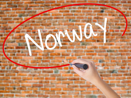 Woman Hand Writing Norway  with black marker on visual screen. Isolated on bricks. Business concept. Stock Photo
