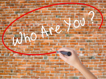 Woman Hand Writing Who Are You with black marker on visual screen. Isolated on bricks. Business concept. Stock Photo Stock Photo