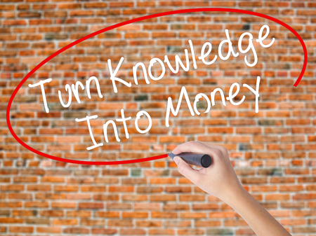 Woman Hand Writing Turn Knowledge Into Money with black marker on visual screen. Isolated on bricks. Business concept. Stock Photo Stock Photo