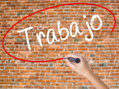 Woman Hand Writing Trabajo  ( work in Spanish) with black marker on visual screen. Isolated on bricks. Business concept. Stock Photo