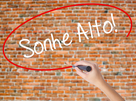 Woman Hand Writing Sonhe Alto! (Dream Big in Portuguese) with black marker on visual screen. Isolated on bricks. Business, technology, internet concept. Stock Photo Imagens