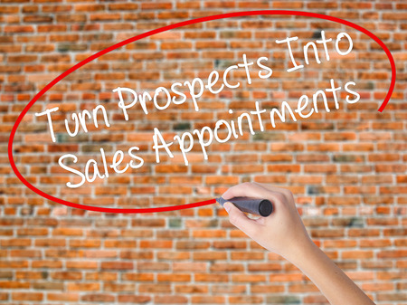 Woman Hand Writing Turn Prospects Into Sales Appointments with black marker on visual screen. Isolated on bricks. Business, technology, internet concept. Stock  Photo Stock Photo