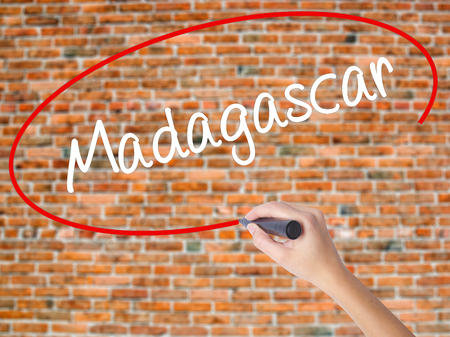 fort dauphin: Woman Hand Writing Madagascar with black marker on visual screen. Isolated on bricks. Business concept. Stock Photo