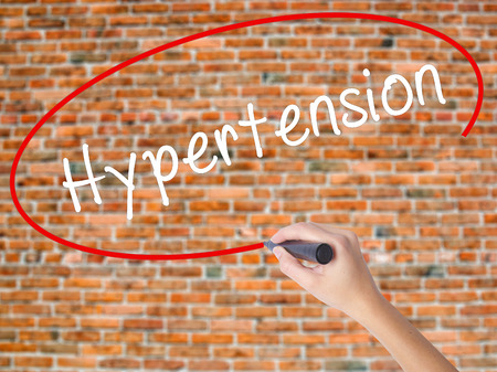 definition define: Woman Hand Writing Hypertension with black marker on visual screen. Isolated on bricks. Business concept. Stock Photo Stock Photo