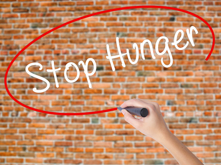 malnutrition: Woman Hand Writing  Stop Hunger with black marker on visual screen. Isolated on bricks. Business concept. Stock Photo