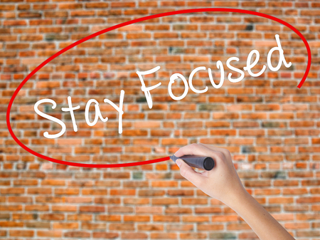 Woman Hand Writing Stay Focused with black marker on visual screen. Isolated on bricks. Business,  technology, internet concept. Stock Photo