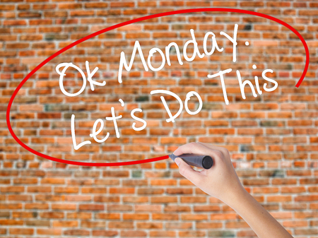 Woman Hand Writing Ok Monday. Lets Do This with black marker on visual screen. Isolated on bricks. Business concept. Stock Photo