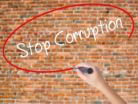 immoral: Woman Hand Writing Stop Corruption with black marker on visual screen. Isolated on bricks. Business concept. Stock Photo