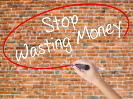 Woman Hand Writing Stop Wasting Money with black marker on visual screen. Isolated on bricks. Business concept. Stock Photo