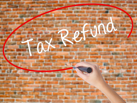 Woman Hand Writing Tax Refund with black marker on visual screen. Isolated on bricks. Business concept. Stock Photo