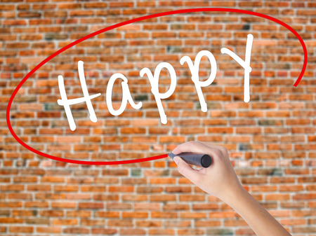 Woman Hand Writing Happy black marker on visual screen. Isolated on bricks. Business concept. Stock Photo