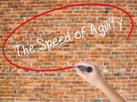 Woman Hand Writing The Speed of Agility with black marker on visual screen. Isolated on bricks. Business concept. Stock Photo