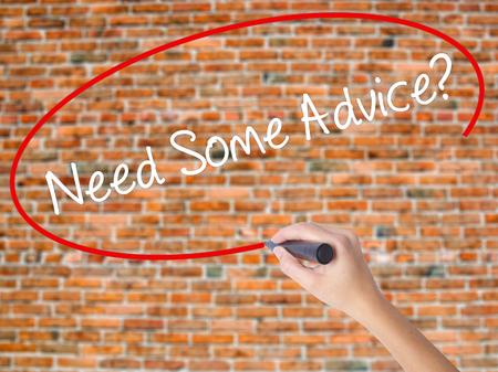Escritura de la mano de la mujer ¿Necesita un consejo? con marcador negro en la pantalla visual. Aislados en ladrillos. Concepto de negocio. Foto de stock