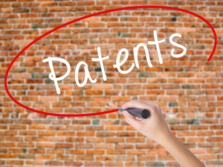 Woman Hand Writing Patents with black marker on visual screen. Isolated on bricks. Business concept. Stock Photo