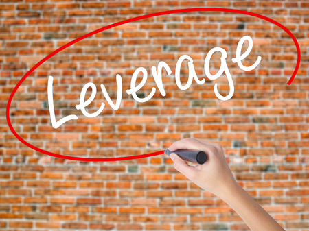 leverage: Woman Hand Writing Leverage with black marker on visual screen. Isolated on bricks. Business concept. Stock Photo