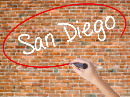 Woman Hand Writing San Diego with black marker on visual screen. Isolated on bricks. Business concept. Stock Photo
