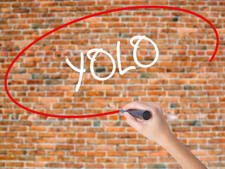Woman Hand Writing YOLO (You Only Live Once) with black marker on visual screen. Isolated on bricks. Business concept. Stock Photo