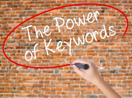 Woman Hand Writing The Power of Keywords with black marker on visual screen. Isolated on bricks. Business concept. Stock Photo Stock Photo