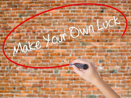 Woman Hand Writing Make Your Own Luck with black marker on visual screen. Isolated on bricks. Business concept. Stock Photo