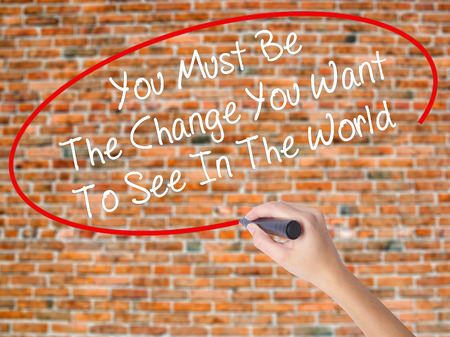 Woman Hand Writing You Must Be The Change You Want To See In The World with black marker on visual screen. Isolated on bricks. Business concept. Stock Photo