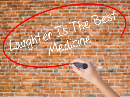 Woman Hand Writing Laughter Is The Best Medicine  with black marker on visual screen. Isolated on bricks. Business concept. Stock Photo Stock Photo