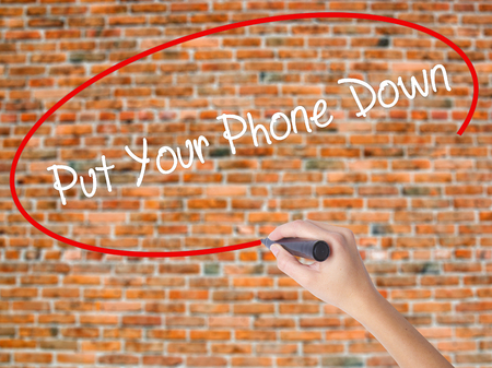 Woman Hand Writing Put Your Phone Down with black marker on visual screen. Isolated on bricks. Business concept. Stock Photo