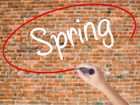 eastertime: Woman Hand Writing Spring with black marker on visual screen. Isolated on bricks. Business concept. Stock Photo Stock Photo
