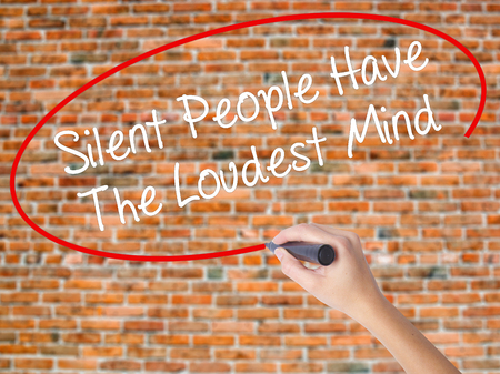 Woman Hand Writing Silent People Have The Loudest Mind with black marker on visual screen. Isolated on bricks. Business concept. Stock Photo