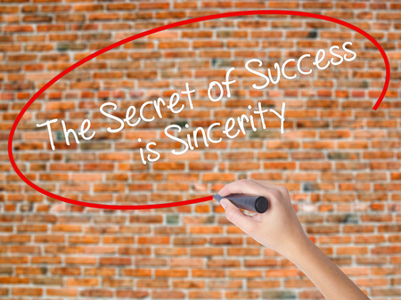 Woman Hand Writing The Secret of Success is Sincerity with black marker on visual screen. Isolated on bricks. Business concept. Stock Photo Stock Photo - 71604813