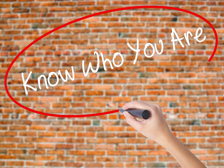 Woman Hand Writing Know Who You Are with black marker on visual screen. Isolated on bricks. Business, technology, internet concept.