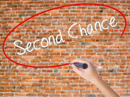 Woman Hand Writing Second Chance with black marker on visual screen. Isolated on bricks. Business, technology, internet concept. Stock Photo Stock Photo