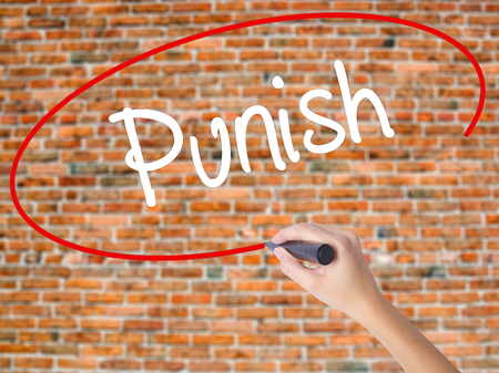 Woman Hand Writing Punish with black marker on visual screen. Isolated on bricks. Business concept. Stock Photo