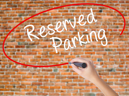 Woman Hand Writing Reserved Parking with black marker on visual screen. Isolated on bricks. Business concept. Stock Photo Stock Photo
