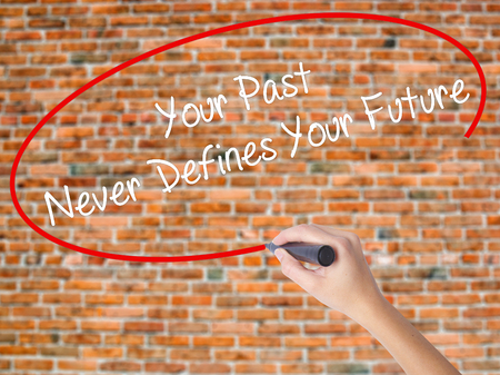 defines: Woman Hand Writing Your Past Never Defines Your Future with black marker on visual screen. Isolated on bricks. Business concept. Stock Photo