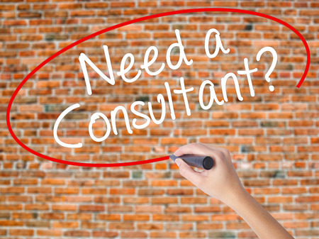Woman Hand Writing Need a Consultant? with black marker on visual screen. Isolated on bricks. Business concept. Stock Photo