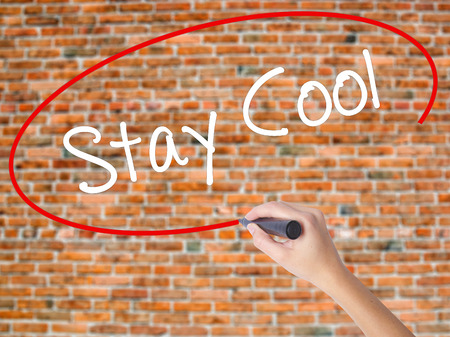 Woman Hand Writing Stay Cool   with black marker on visual screen. Isolated on bricks. Business concept. Stock Photo Stock Photo