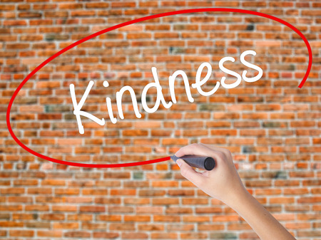 solicitude: Woman Hand Writing Kindness with black marker on visual screen. Isolated on bricks. Business, technology, internet concept.