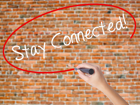 Woman Hand Writing Stay Connected! with black marker on visual screen. Isolated on bricks. Business concept. Stock Photo
