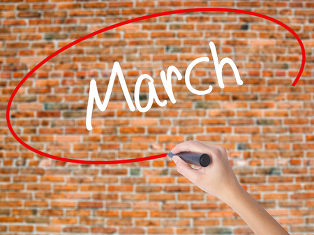 Woman Hand Writing March with black marker on visual screen. Isolated on bricks. Business concept. Stock Photo Stock Photo