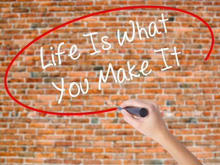 street wise: Woman Hand Writing Life Is What You Make It with black marker on visual screen. Isolated on bricks. Business, technology, internet concept. Stock Photo