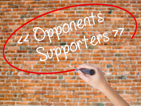 Woman Hand Writing Opponents - Supporters with black marker on visual screen. Isolated on bricks. Business concept. Stock Photo Stock Photo