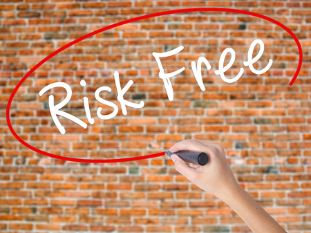 Woman Hand Writing Risk Free with black marker on visual screen. Isolated on bricks. Business concept. Stock Photo Stock Photo