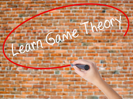 Woman Hand Writing Learn Game Theory with black marker on visual screen. Isolated on bricks. Business concept. Stock Photo
